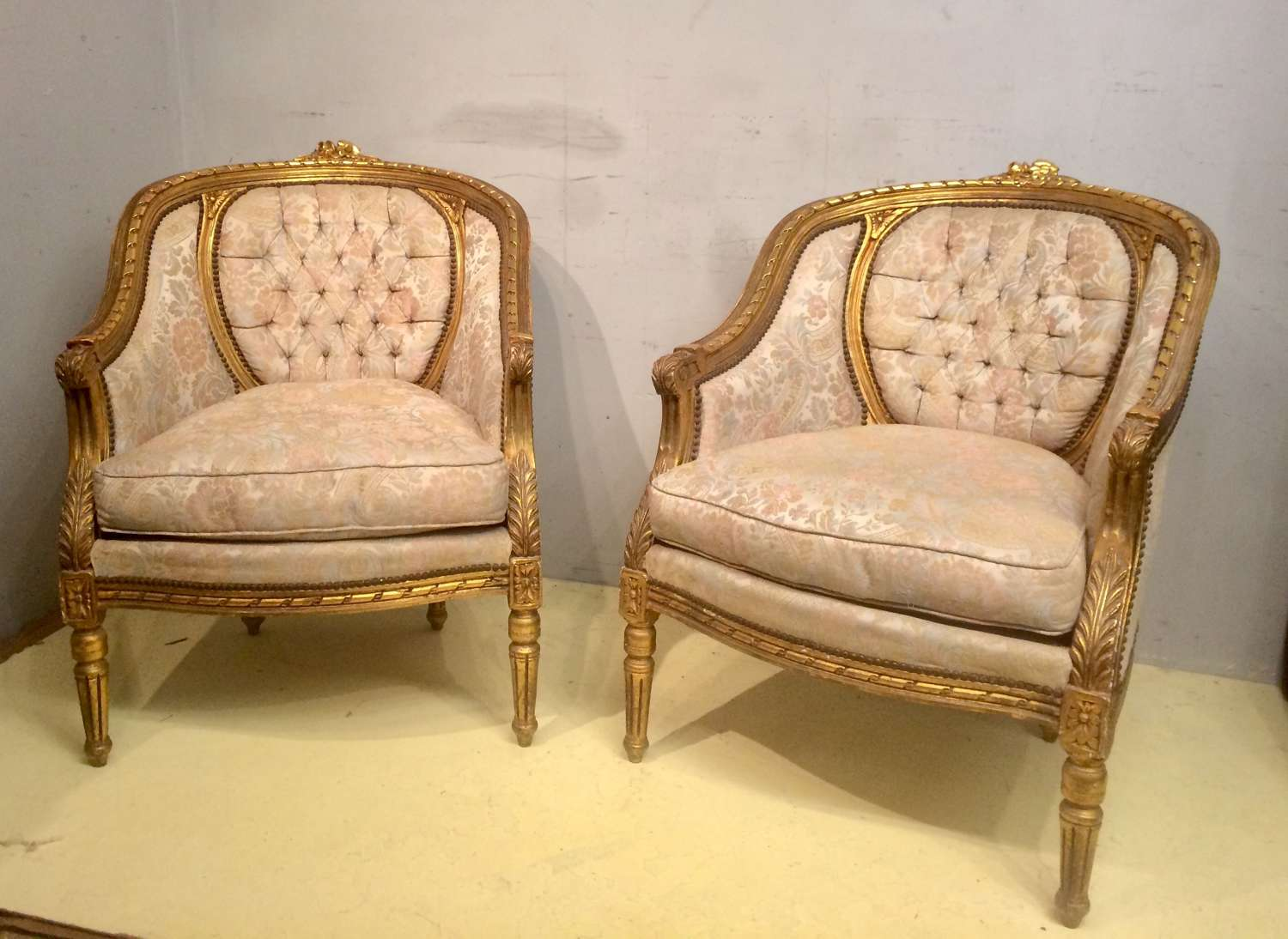 A pair of carved giltwood tub chairs in the French style.